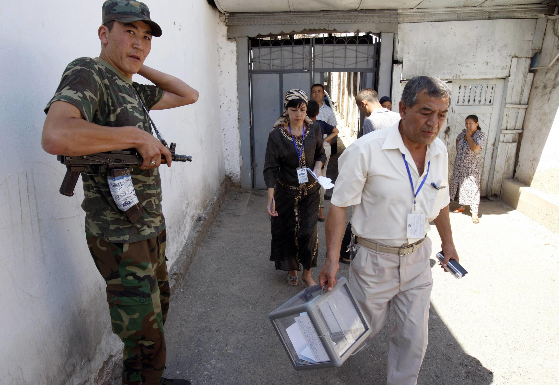 Сотрудники местной избирательной комиссии с переносной урной для голосования в сопровождении солдат в ходе референдума в киргизском городе Оше 27 июня 2010 года