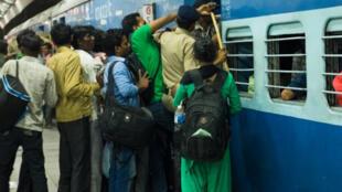 Dans la gare de New Delhi NDLS, devant la cohue pour tenter de monter à bord du train, un policier tente de « dompter » la foule.