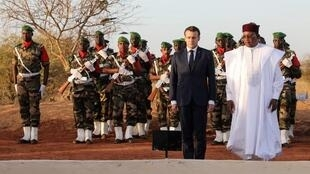 President Emmanuel Macron of France (centre) and Niger's President Mahamadou Issoufou (right) visited the cemetery where 71 soldiers killed in a terrorist attack are buried.