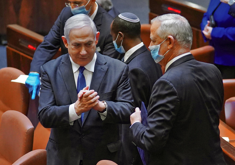 El primer ministro de Israel, Benjamin Netanyahu (izq), dialoga con Benny Gantz, con quien se alternará en el cargo, durante la ceremonia de jura del nuevo gobierno el 17 de mayo de 2020 en Jerusalén