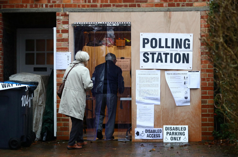 Le 12 décembre 2019, un couple s'apprête à voter lors des élections générales anticipées dans un garage reconverti en bureau de vote, à Londres.
