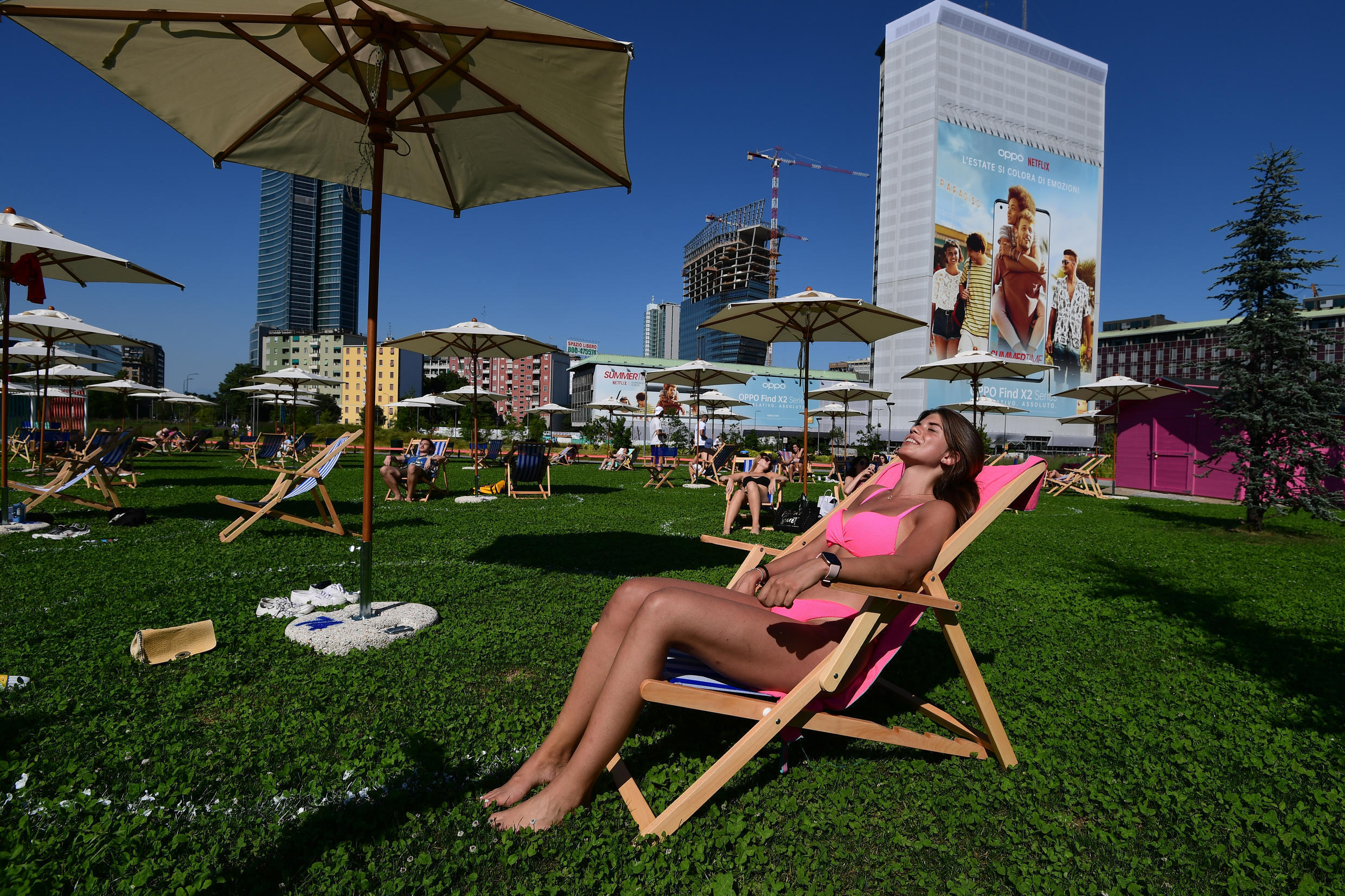 "People sunbathe in a kind of green beach amid the skyscrapers called ""Il Lido Bam"" located in the ""Library trees"" park on June 23, 2020 in the Porta Nuova district, central Milan."