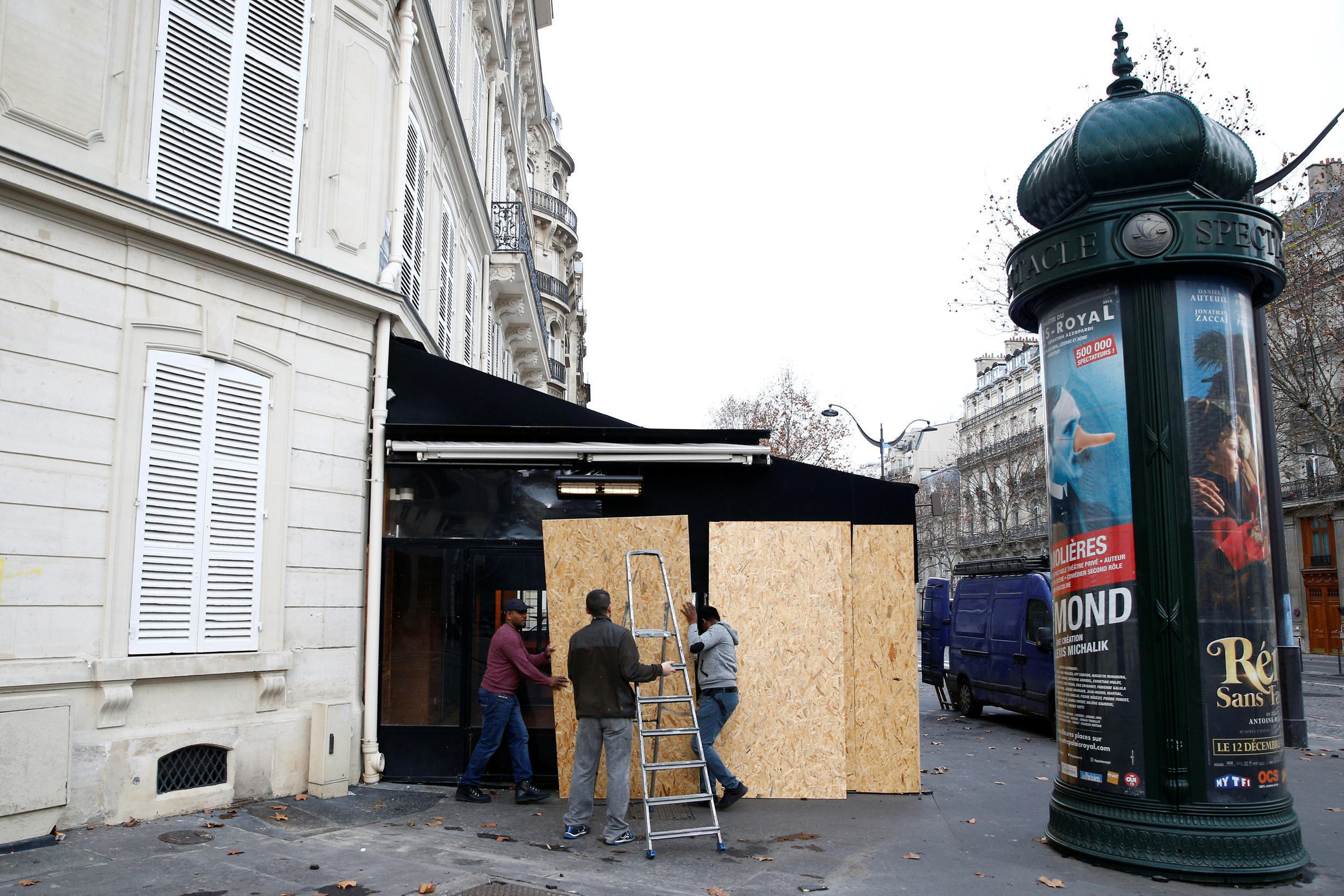 """Workmen remove protective wood panels outside a restaurant the day after clashes during a national day of protest by the """"yellow vests"""" movement in Paris, France, December 9, 2018."""