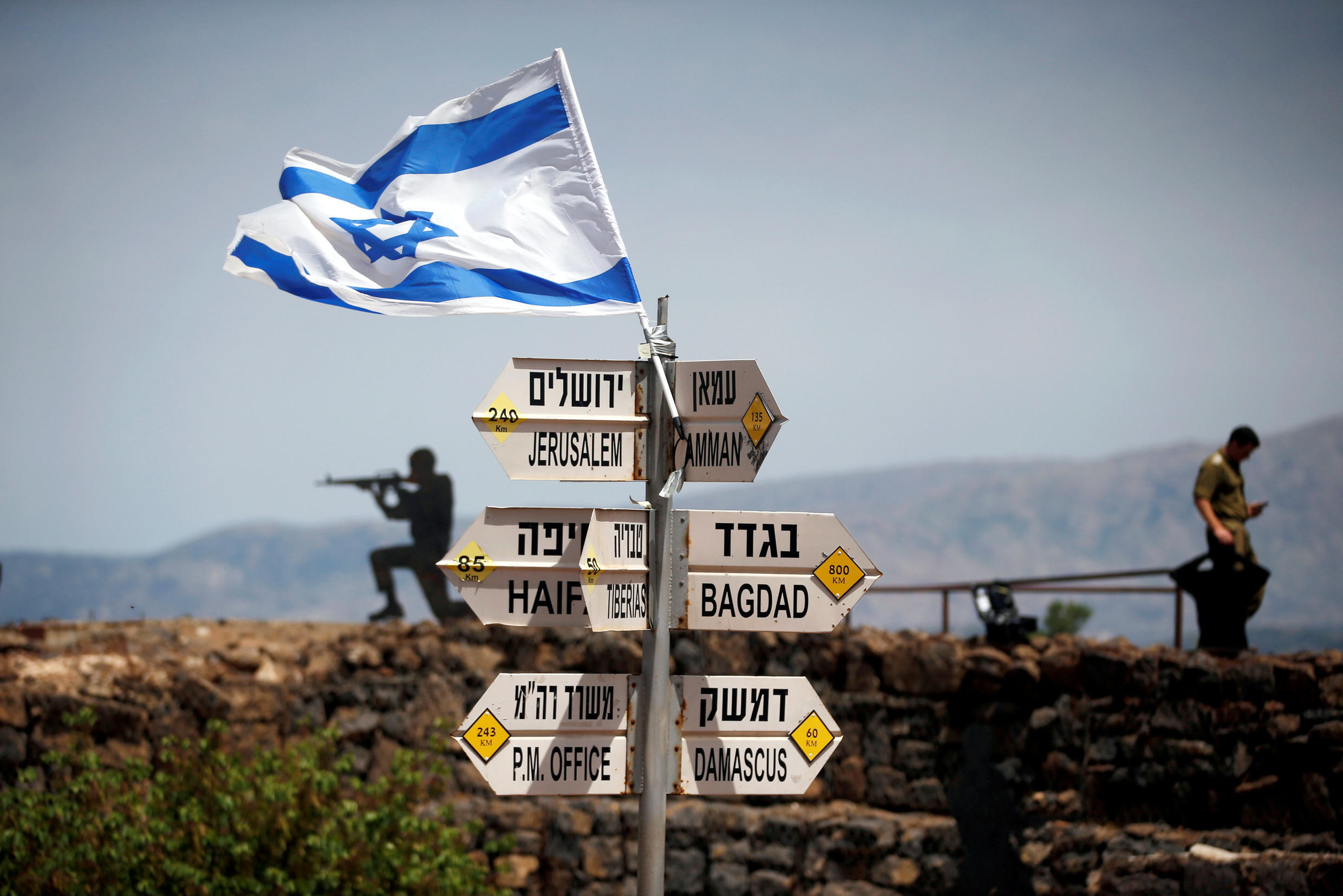 An Israeli soldier stands near a signpost on Mount Bental, an observation post in the Israeli-occupied Golan Heights overlooking Syria, 10 May 2018.