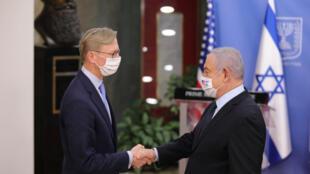 US special representative for Iran Brian Hook (L) and Israeli Prime Minister Benjamin Netanyahu (R), both wearing protective masks, shake hands at the premier's office in Jerusalem