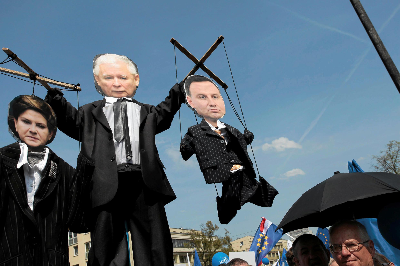 Une marionnette du chef du parti conservateur au pouvoir en Pologne Jaroslaw Kaczynski tenant entre ses doigts la Première ministre Beata Szydlo et le président Andrzej Duda.
