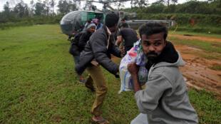 Vítimas da enchente descarregam alimentos e ajuda humanitária de um helicóptero da Força Aérea Indiana em Kerala, em 21 de agosto de 2018.