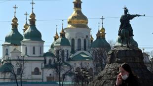 Una mujer con mascarilla habla por teléfono cerca de la Catedral de Santa Sofía de Kiev el 26 de marzo de 2020