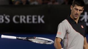 O sérvio Novak Djokovic joga a raquete irritado durante jogo contra o suíço Stanislas Wawrinka.
