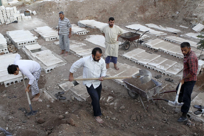 Những người tình nguyện chôn xác các nạn nhân sau một cuộc không kích của quân chính phủ tại Alep ngày 20/08/2012.