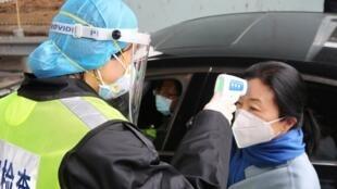 Officier de la sécurité chinoise prenant la température de la passagère d'un véhicule, à Xianning, non loin de Wuhan, le 24 janvier 2020.