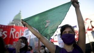 Uma ativista a favor do aborto exibe um lenço verde, emblema da discriminalização da IVG, perante o congresso em Buenos Aires, em uma manifestação em 28 de maio de 2020.