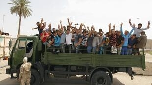 Voluntários são levados por caminhão do Exército para combater a capital Bagdá da chegada dos jihadistas.
