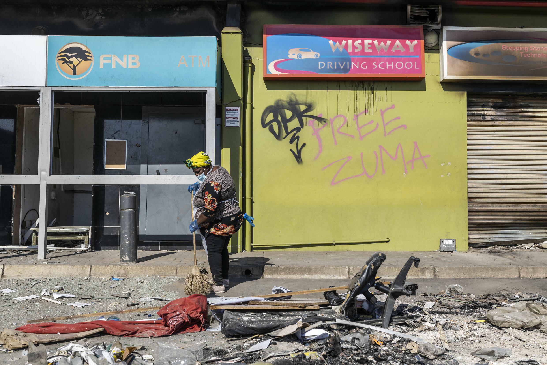 Una mujer barre escombros cerca de un centro comercial saqueado, en Durban, Sudáfrica, el 17 de julio de 2021.