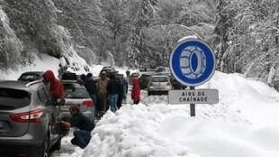 | Snow made some roads impassable in the French Alps and forced these motorists to put chains on their wheels .