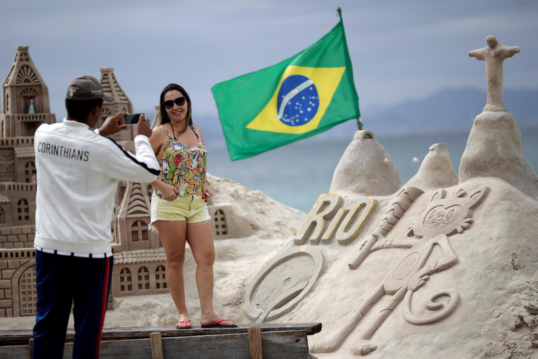 Mulher posa ao lado de escultura de areia do mascote da Olimpíada, Vinícius, na praia de Copacabana, no Rio de Janeiro.