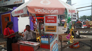 A vendor assists a client to recharge her cell phone airtime at an open air stall in Kinshasa, Democratic Republic of Congo January 1, 2019.