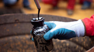 A worker collects a crude oil sample at an oil well operated by Venezuela's state oil company PDVSA in Morichal, Venezuela.