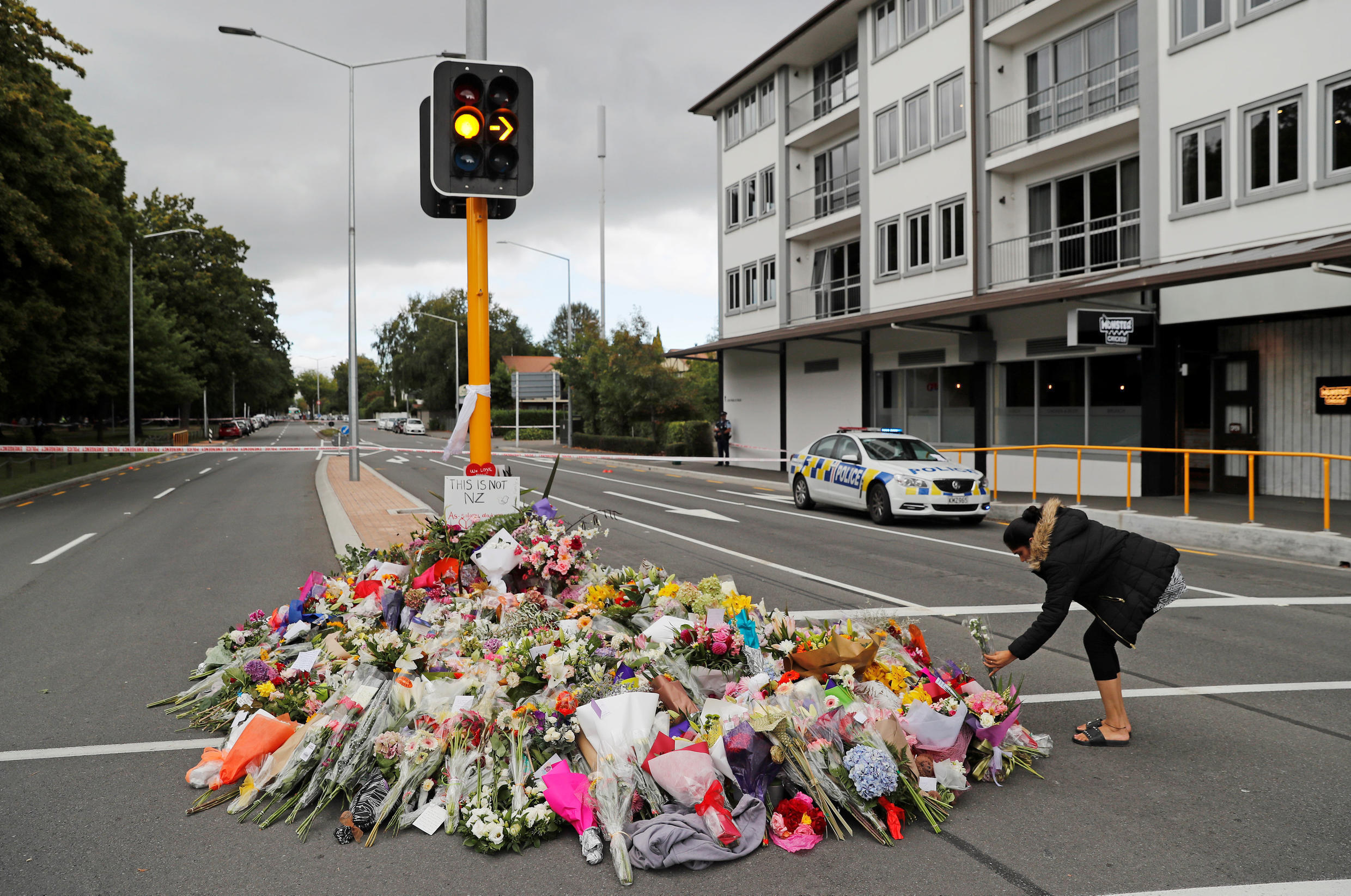 A woman places flowers at a memorial as a tribute to victims of the mosque attacks, near a police line outside Masjid Al Noor in Christchurch, New Zealand, March 16, 2019.