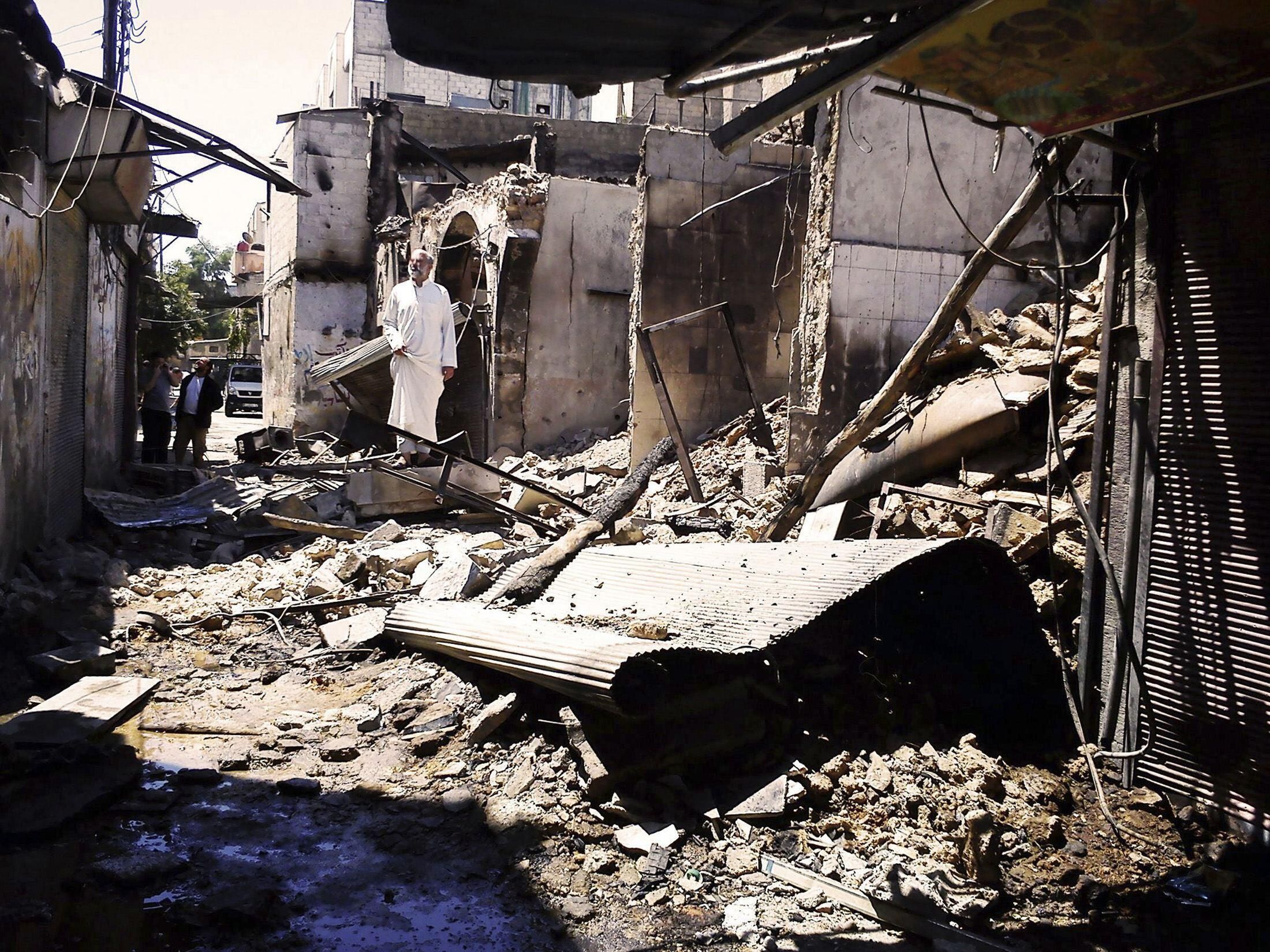 People look at damage at al-Midan neighbourhood in Damascus, 23 July, 2012