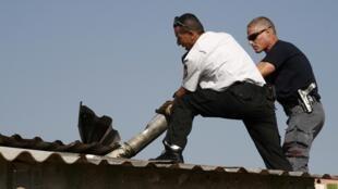 Израильский пожарный и полицейский эксперт по взрывчатым веществам извлекают остатки ракеты, выпущенной с территории Ливана, из крыши здания в Мошав Нетуа в Восточной Галилее 29/11/2011