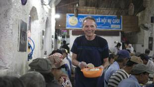 Ông John Kelly, tình nguyện viên người Mỹ nguyên là giám đốc bưu điện, đang phục vụ tại một quán Nụ Cười ở Saigon.