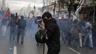 Un manifestant se protège d'émanations de gaz lacrymogène à Athènes pendant la grève générale de 24h