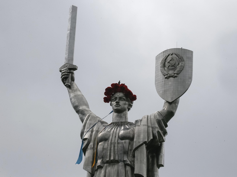 Монумент «Родина-мать» в Киеве с гербом СССР на щите и с маковым венком, установленным в честь 8 мая