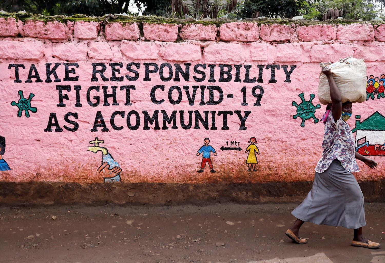 Une femme passe devant un mur peint d'un slogan appelant à la responsabilité de tous dans la lutte contre le Covid-19 à Nairobi, au Kenya.
