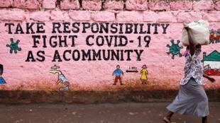 Une femme passe devant un mur peint d'un slogan appelant à la responsabilité de tous dans la lutte contre le Covid-19 à Nairobi au Kenya.
