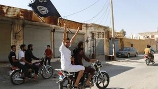 A moto, agitant le drapeau noir des jihadistes, les habitants de Tabqa célèbrent la prise de leur localité par les combattants de l'Etat islamique, le 24 août 2014.