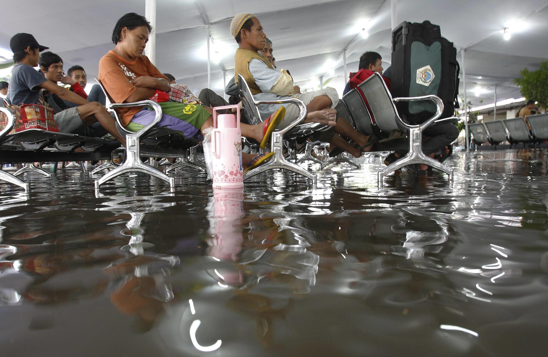 Hành khách đợi tàu tại nhà ga Pasar Senen ở Jakarta, bị ngập nước sau một trận mưa. Ảnh chup ngày 06/09/2010.