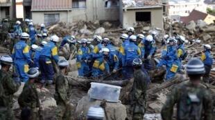 Membros de equipes de resgate fazem buscas por sobreviventes dos deslizamentos de terra em Hiroshima, nesta quinta-feira (21).