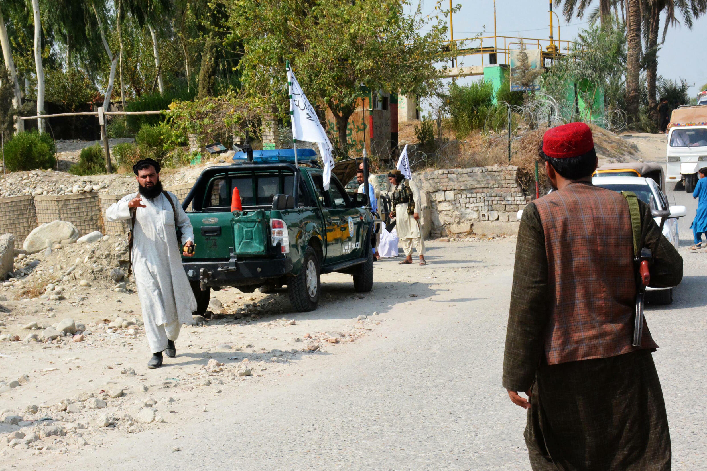 Taliban members inspect near the site of a blast in Jalalabad on September 18