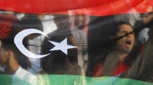 Líbios mostrando a bandeira do país na simbólica Praça Verde em Tripoli na Líbia