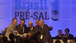 El ministro de Minas y Energía de Brasil, Edison Lobão, con representantes del consorcio que ganó la subasta, este 21 de octubre de 2013 en Río de Janeiro.