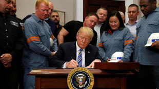 Le président américain Donald Trump a signé à la Maison Blanche les documents qui officialisent l'imposition de taxes sur les importations d'acier et d'aluminium vers les Etats-Unis, le 8 mars 2018.