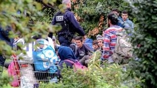 People leave a migrant camp as they are evicted by French authorities near the French port city of Dunkirk, at Grande-Synthe, northern France, on 6 September, 2018.