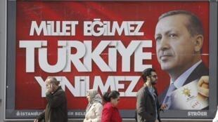 Des Stanbouliotes passent devant une affiche de campagne du Premier ministre Erdogan, le 27 mars.