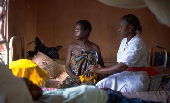 Kadiatu Sama, que não teve cuidados pré-natais e cujo filho nasceu morto, é consolada por uma enfermeira na maternidade do hospital público em Serra Leoa, Unicef/UNI32026/PirozziUNICEF/UNI32026/Pirozzi