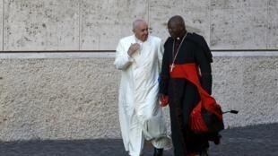 Le pape François discute avec le cardinal Philippe Nakellentuba Ouedraogo avant de présider le synode sur la famille, le 23 octobre 2015 au Vatican.
