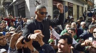Le journaliste algérien Khaled Drareni porté par les manifestants après avoir été brièvement détenu par les forces de police, à Alger le 6 mars 2020.