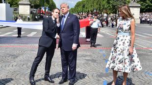 French President Emmanuel Macron (L) with US President Donald Trump and his wife Melania on the Champs Elysées last July