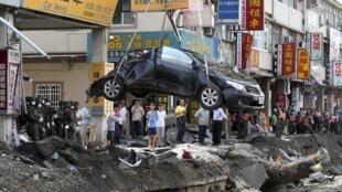 台湾高雄市发生连串大爆炸,救援清理单位正搬移一辆被炸毁轿车  2014年8月2日