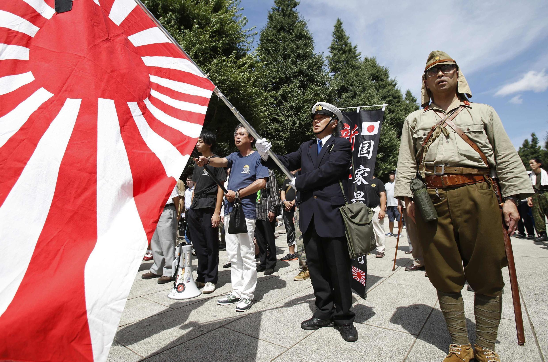 Một nhóm người mang cờ và quân phục Nhật Hoàng đến đền thờ Yasukuni, Tokyo, 15/08/2014. Đây là ngôi đền thường bị coi là biểu tượng của quá khứ quân phiệt Nhật Bản.