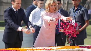 O presidente francês Emmanuel Macron e sua mulher Brigitte Macron jogam pétalas de rosa no memorial Mahatma Gandhi em Nova Déli, na Índia, em março.