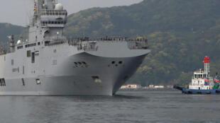 Le navire d'assaut amphibie français Mistral (L) arrive à la base navale Sasebo de la Force d'autodéfense japonaise à Sasebo, préfecture de Nagasaki, au Japon le 29 avril 2017, avant les exercices dans les eaux de Guam.