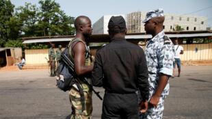 A coté d'un officier de la police nationale de Côte d'Ivoire, un soldat mutin se prépare à quitter le checkpoint à l'entrée de Bouaké, le 16 mai 2017.