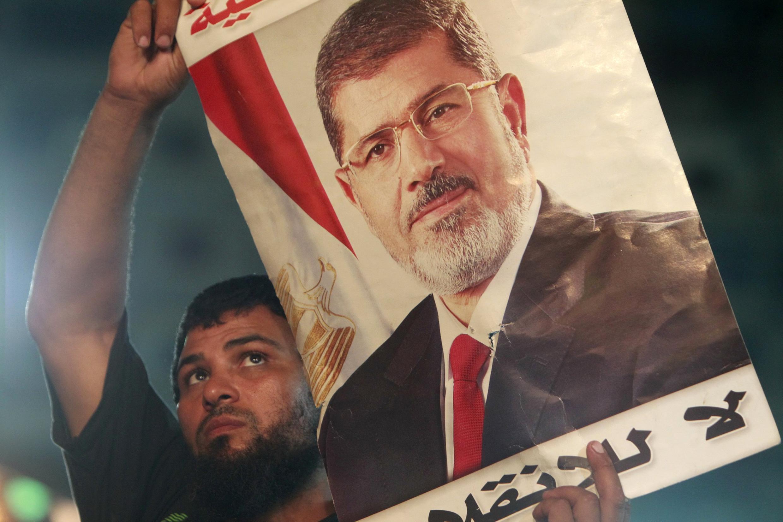 Un pro-Morsi brandit un poster à l'effigie du président déchu Mohamed Morsi, au cours des manifestations devant la mosquée de Rabaa au Caire.