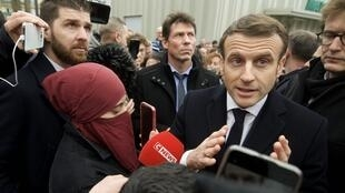 French President Emmanuel Macron, surrounded by journalists as he arrives at the police station in the district of Bourtzwiller, in Mulhouse, February 18, 2020.